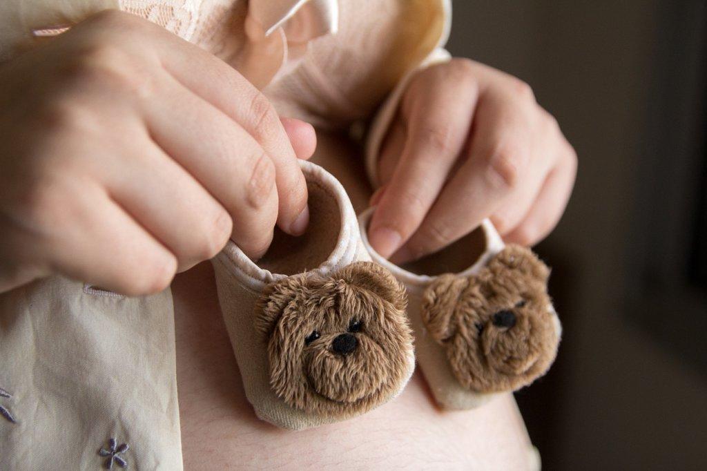 Kobieta w ciąży trzyma słodkie kapcie z misiami