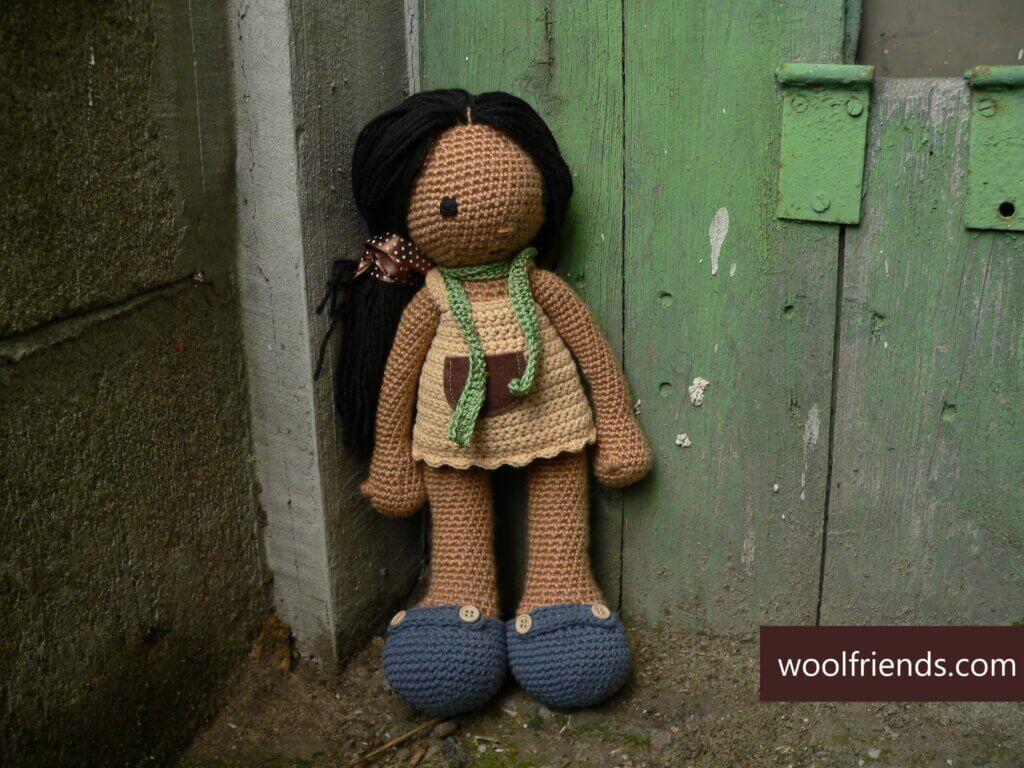 lalka na szydełku na tle starych zielonych drzwi